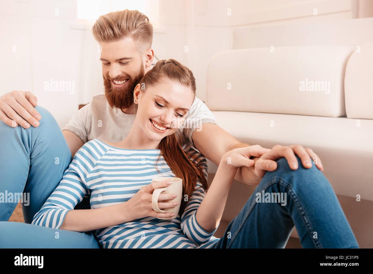 Felice coppia giovane seduti insieme sul pavimento e bere il tè Immagini Stock