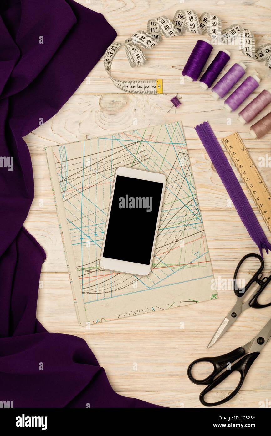 Accessori per il cucito, tessuto, modelli e un telefono cellulare di colore bianco su una luce sullo sfondo di legno. Messa a fuoco selettiva. Foto Stock