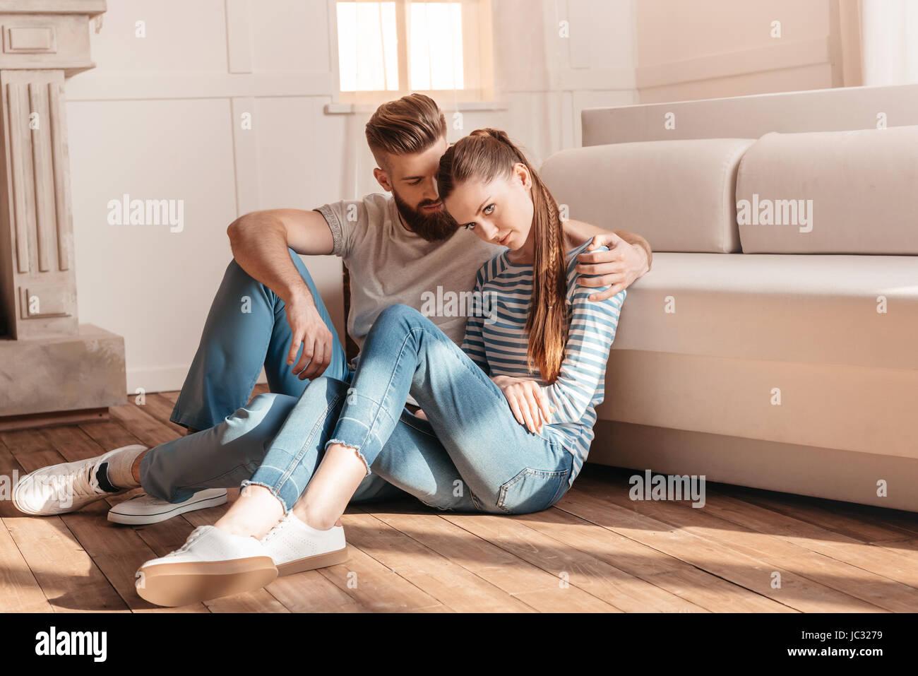 Gara giovane uomo e donna abbracciando e seduto sul pavimento a casa Immagini Stock