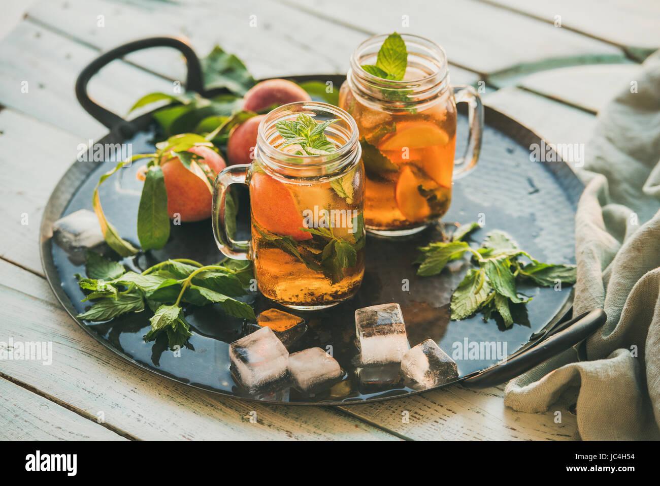 Estate rinfrescante freddo pesca ice tea su tavola in legno rustico Immagini Stock