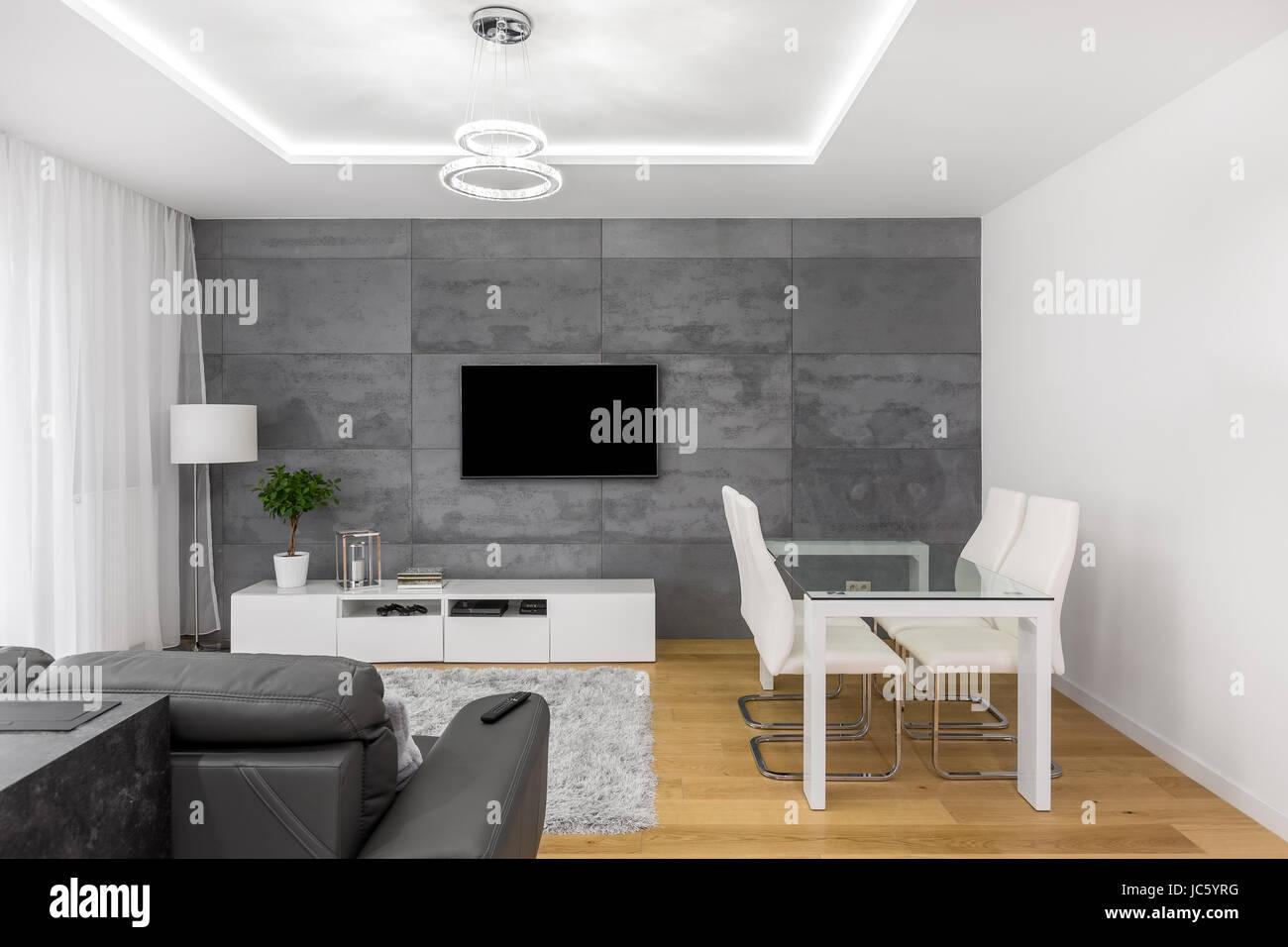 Moderno soggiorno con tavolo in vetro e sedie bianche e tv sulla ...