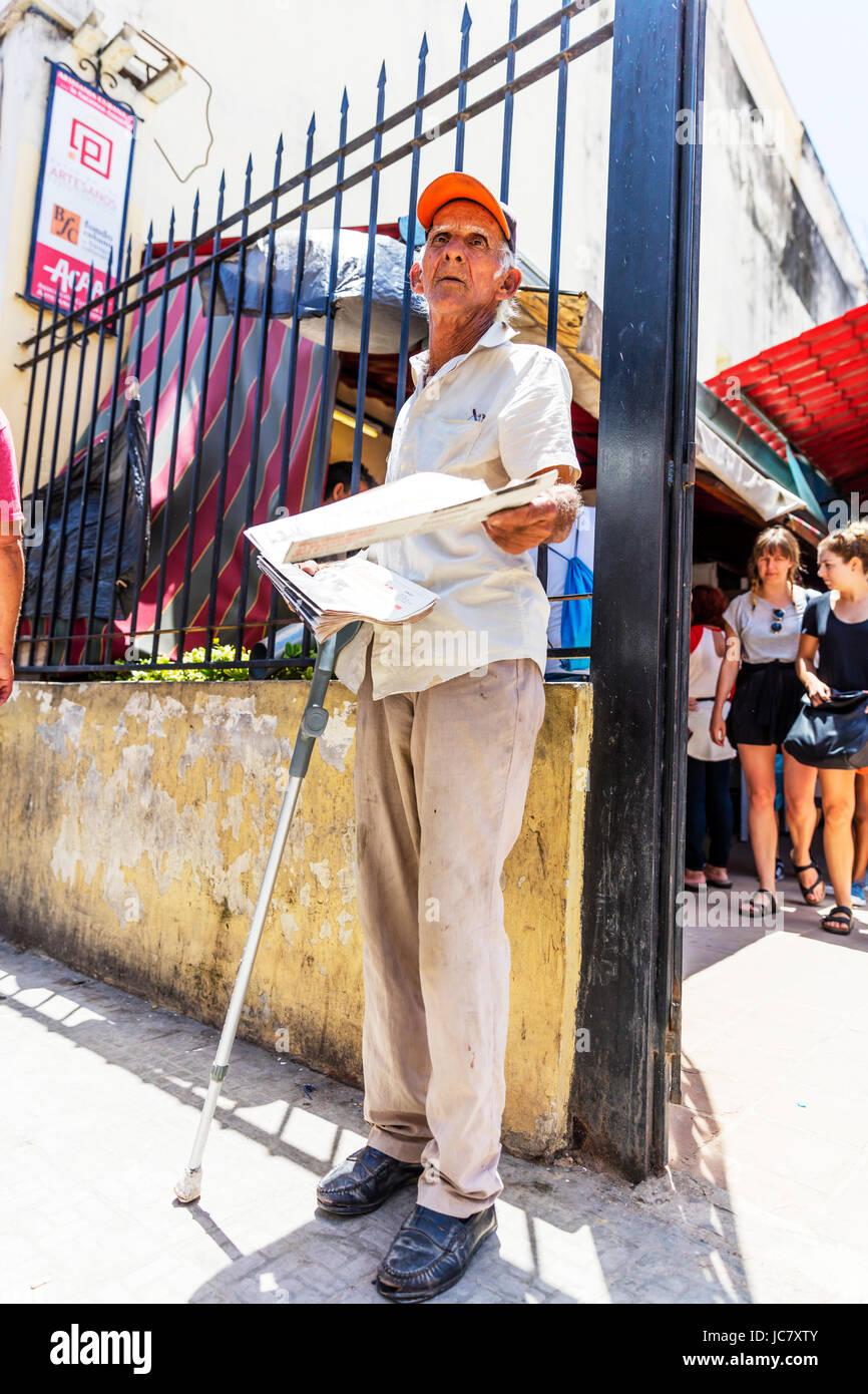Il vecchio uomo di consegnare il quotidiano gratuito in strada di Havana, Cuba, uomo cubano distribuendo depliant, Immagini Stock