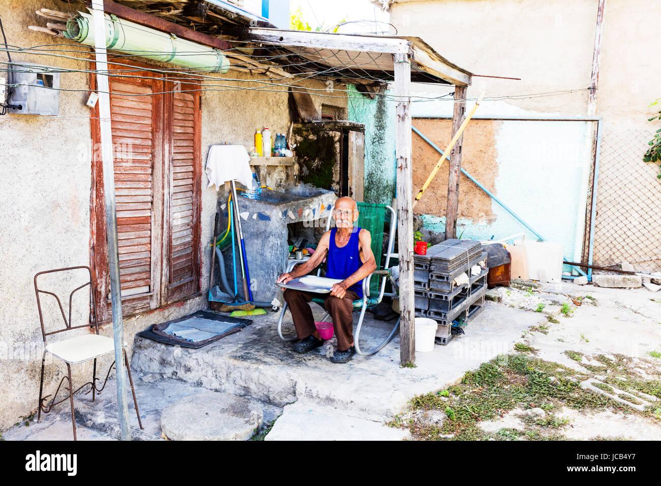 Il vecchio uomo cubano con vassoio di riso sul giro, ordinamento di riso, conteggio di granelli di riso, giardino Immagini Stock