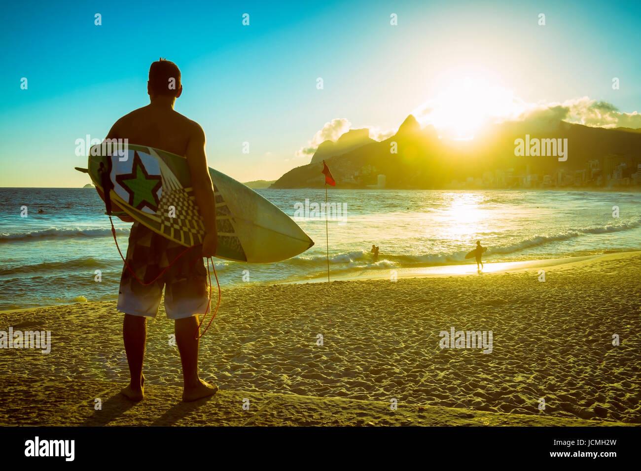Silhouette al tramonto del surfer con il suo bordo wat a Arpching il tramonto surf a Arpoador, la spiaggia di Ipanema, Immagini Stock