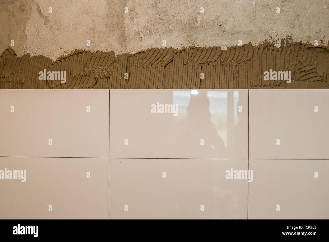Ceramista di piastrella applicato adesivo sulla parete bellissime