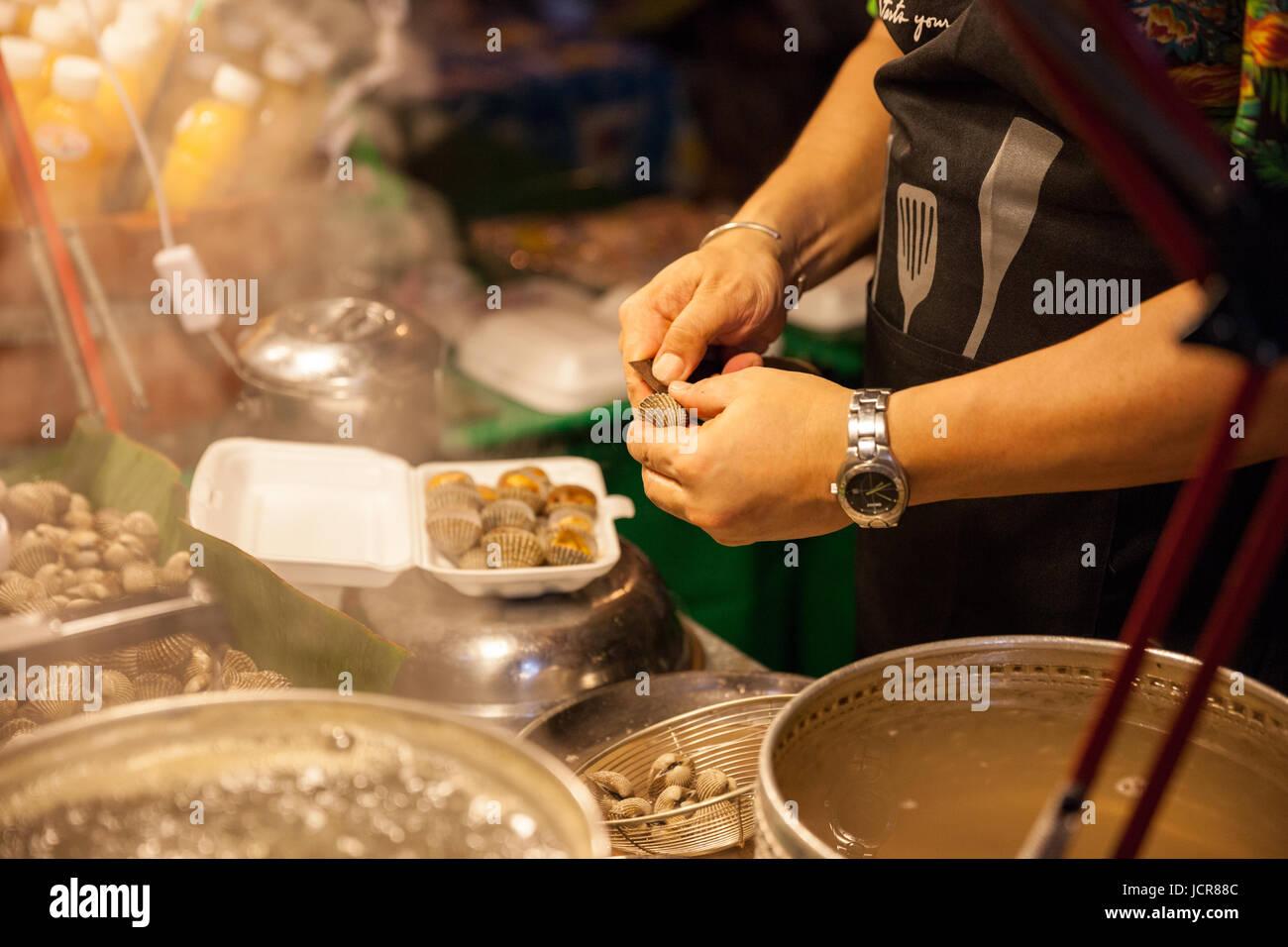 CHIANG MAI, Thailandia - 27 agosto: Uomo preparare le vongole in vendita al mercato di domenica (walking street) Foto Stock
