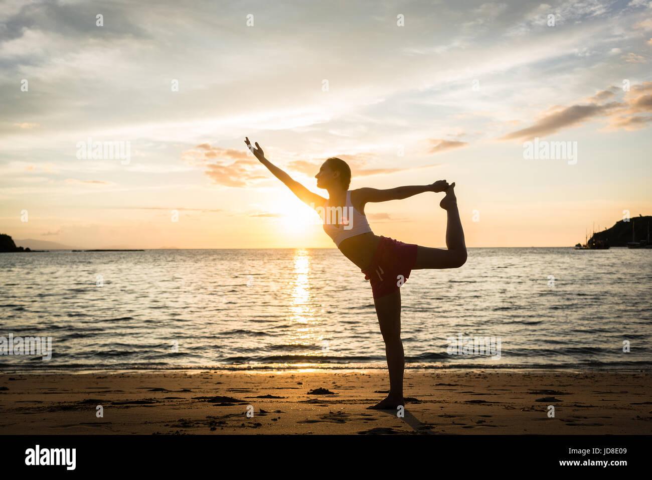 Lunghezza piena vista laterale di un accoppiamento donna pratica sulla spiaggia. La prua permanente tirando pongono Foto Stock
