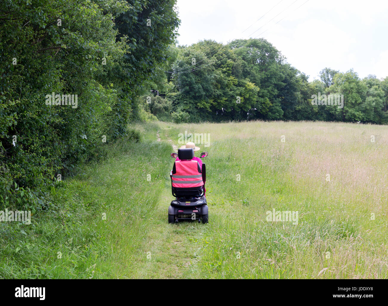 Una donna in sella a una mobilità scooter dando accesso per disabili in campagna, Kent, England Regno Unito Immagini Stock
