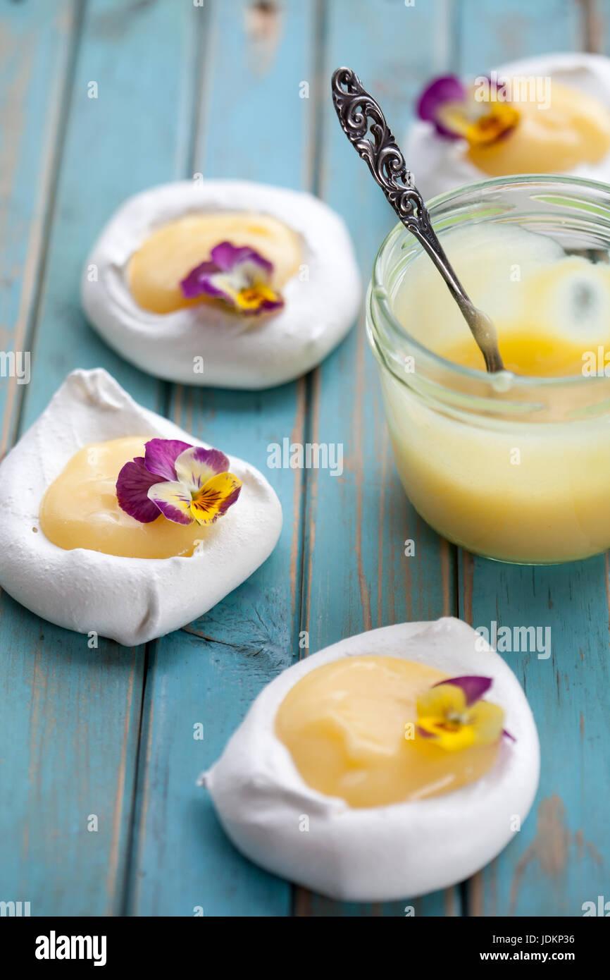 Mini pavlova con cagliata di limone e fiori Immagini Stock