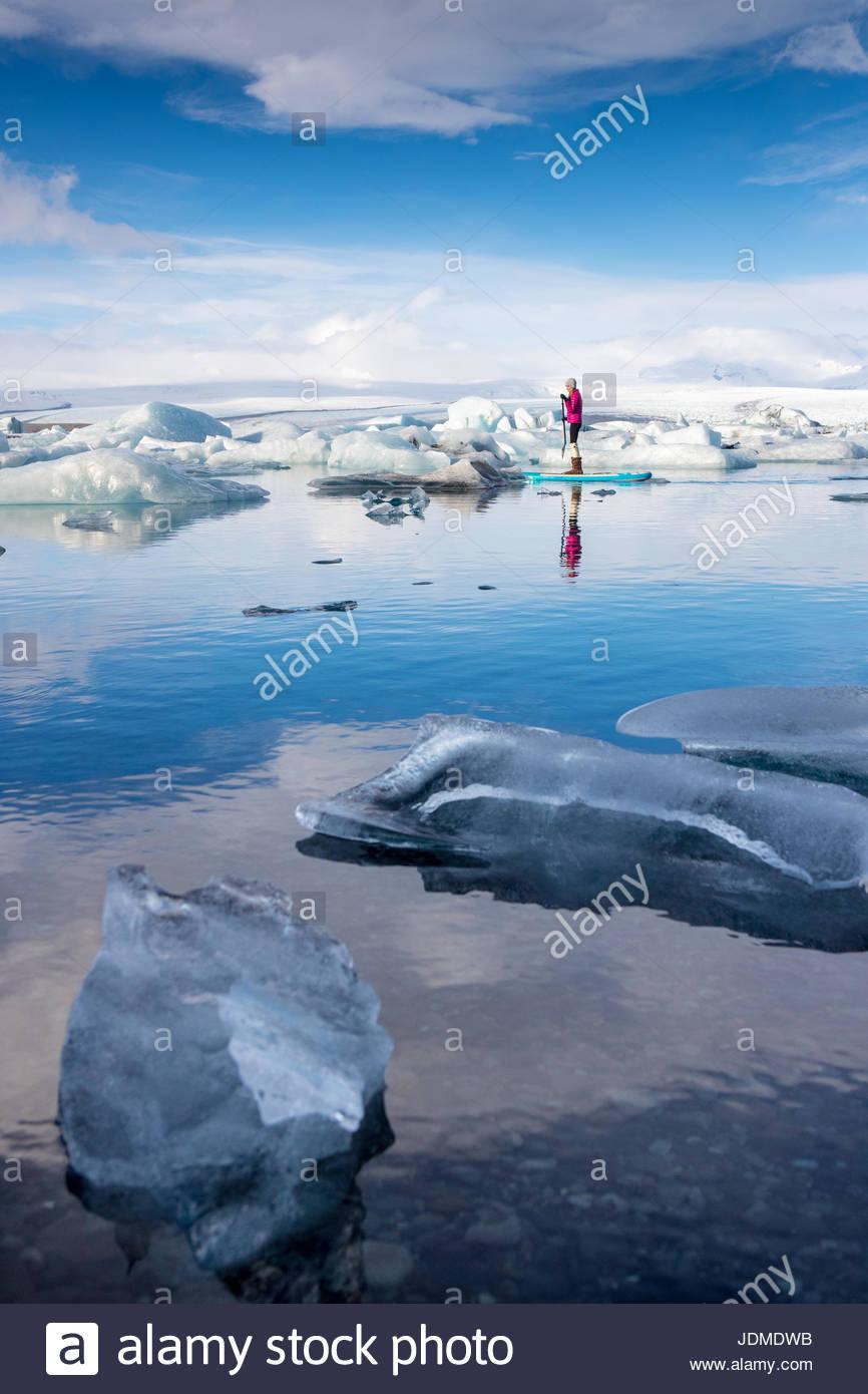 Una donna su un gonfiabile paddleboard pagaiando sul Jokulsarlon laguna glaciale. Immagini Stock
