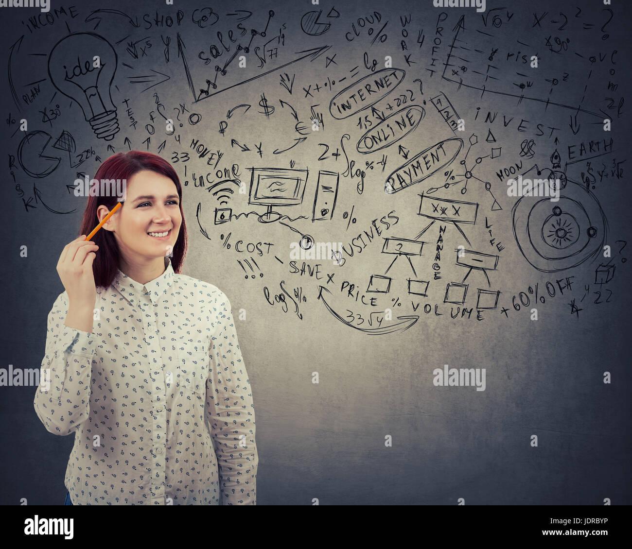 Ritratto perplesso donna giovane studente di pensare con una matita appuntita per testa, ha molte idee, sognando. Immagini Stock