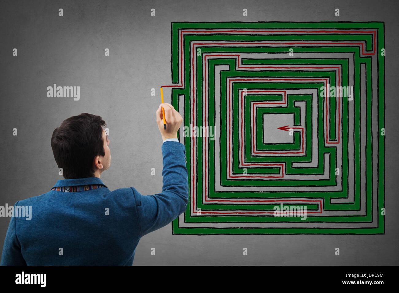 Giovane imprenditore tenendo una matita in mano a cercare di trovare la soluzione di un fantasioso labirinto quadrato, Immagini Stock