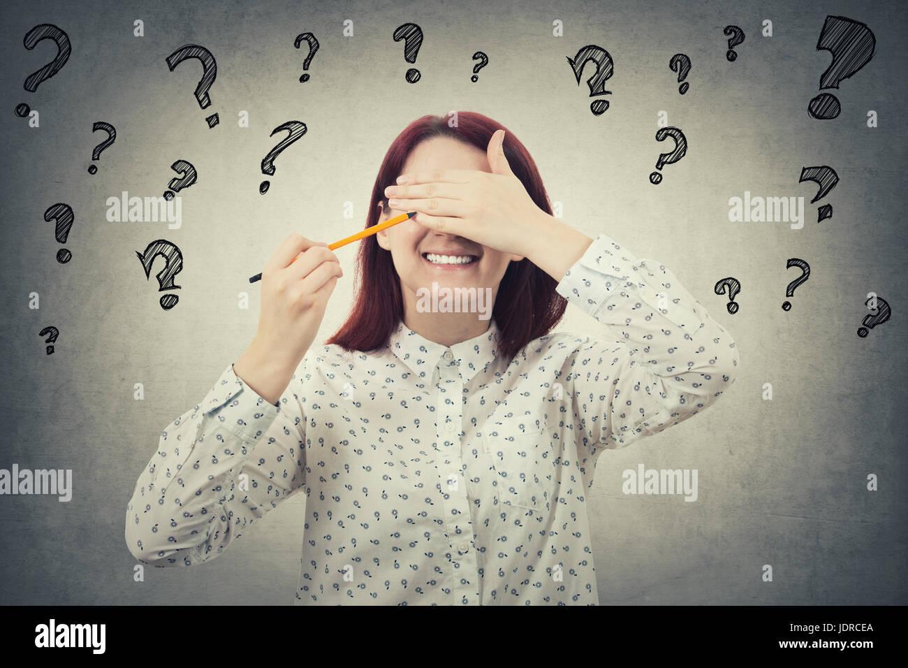 Ritratto di sorridente giovane donna che copre gli occhi con la mano il tentativo di richiamare un'altra espressione Immagini Stock
