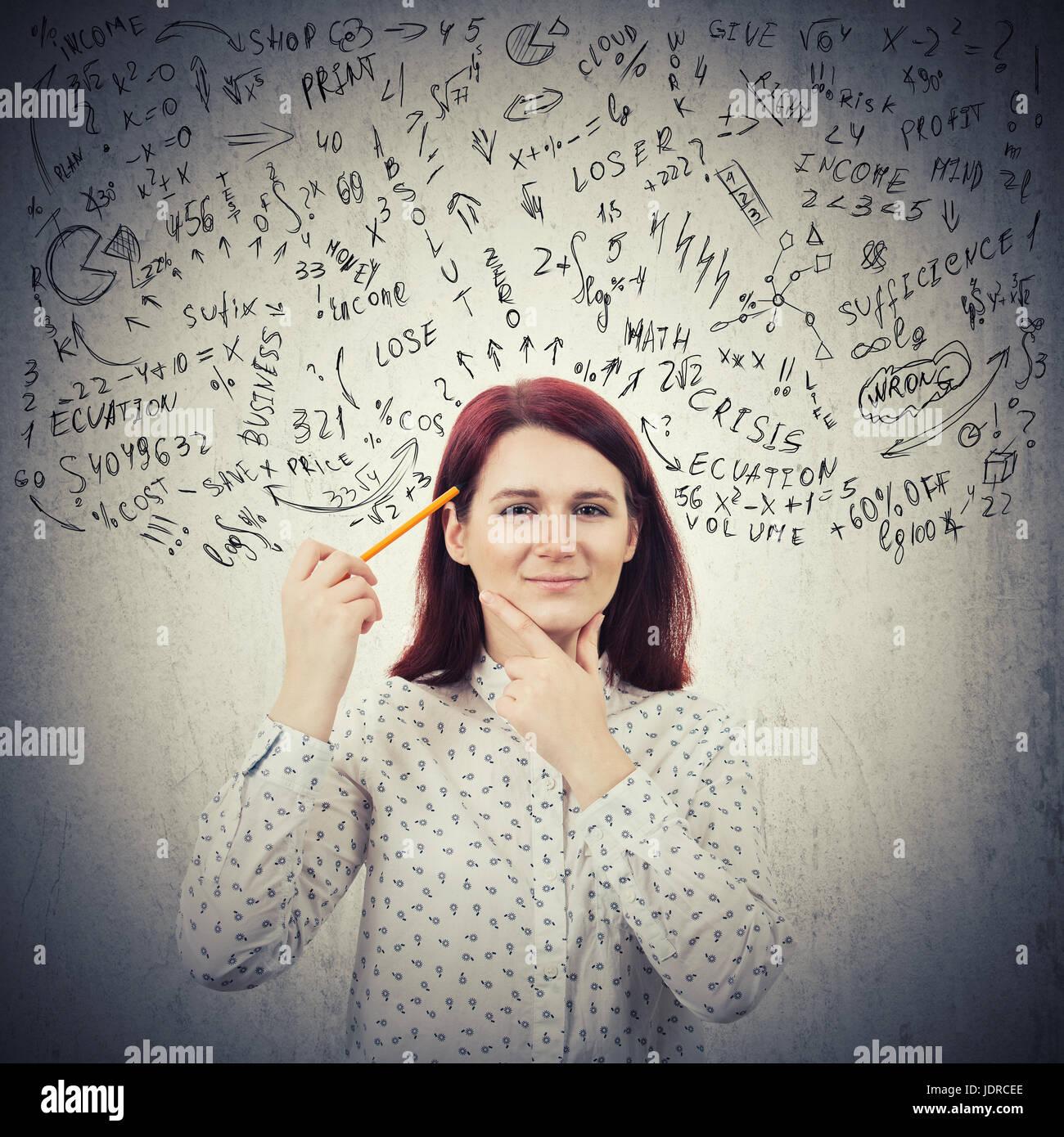 Ritratto di giovane e sorridente, perplesso imprenditrice, tenendo in mano una matita per la sua testa la creazione Immagini Stock