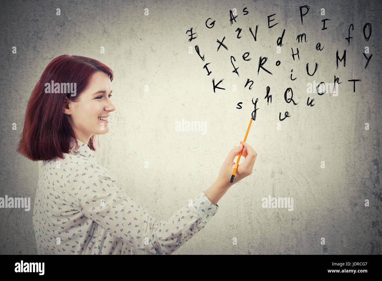 Giovane imprenditrice, tenendo in mano una matita in mano disegno lettere dell'alfabeto. Educazione e comunicazione Foto Stock
