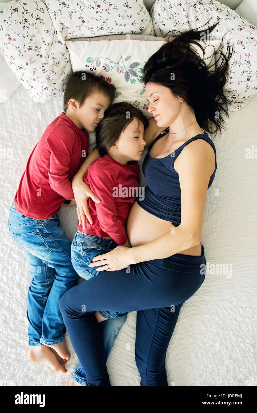 Bella incinta giovane madre e i suoi due bambini, ragazzi, giacenti nel letto di casa Foto Stock
