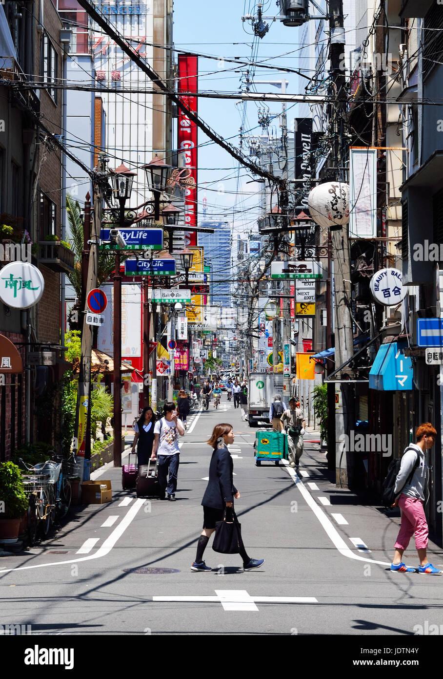 Un ufficio giapponese donna attraversa la strada di fronte a un vicolo stretto nel quartiere Namba di Osaka, Giappone Immagini Stock