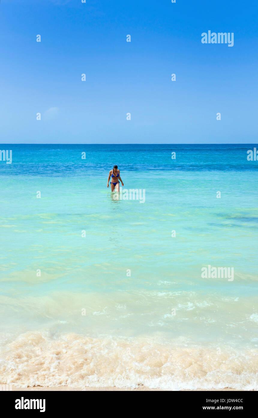 Donna in mare in spiaggia di fronte al Dunn's River Falls, Giamaica Foto Stock