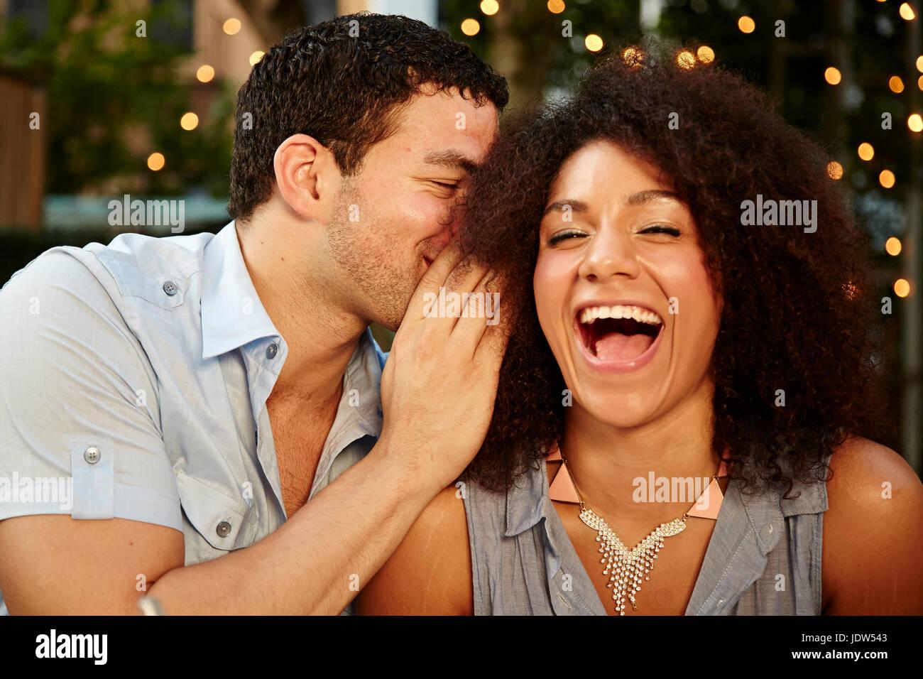 Giovane uomo whispering a ridere donna al party in giardino Foto Stock