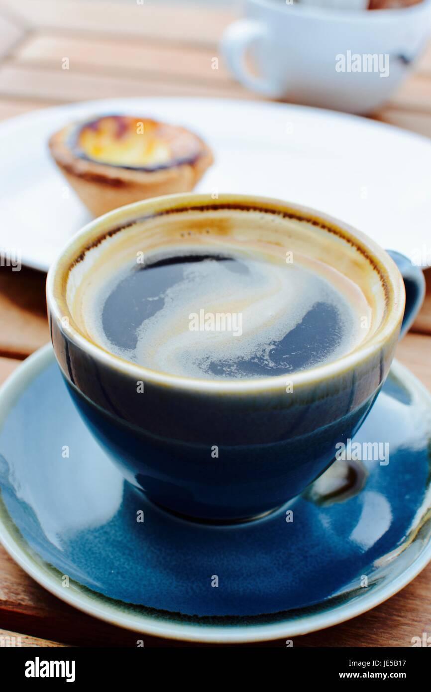 Nero caffè con una torta portoghese in background Immagini Stock