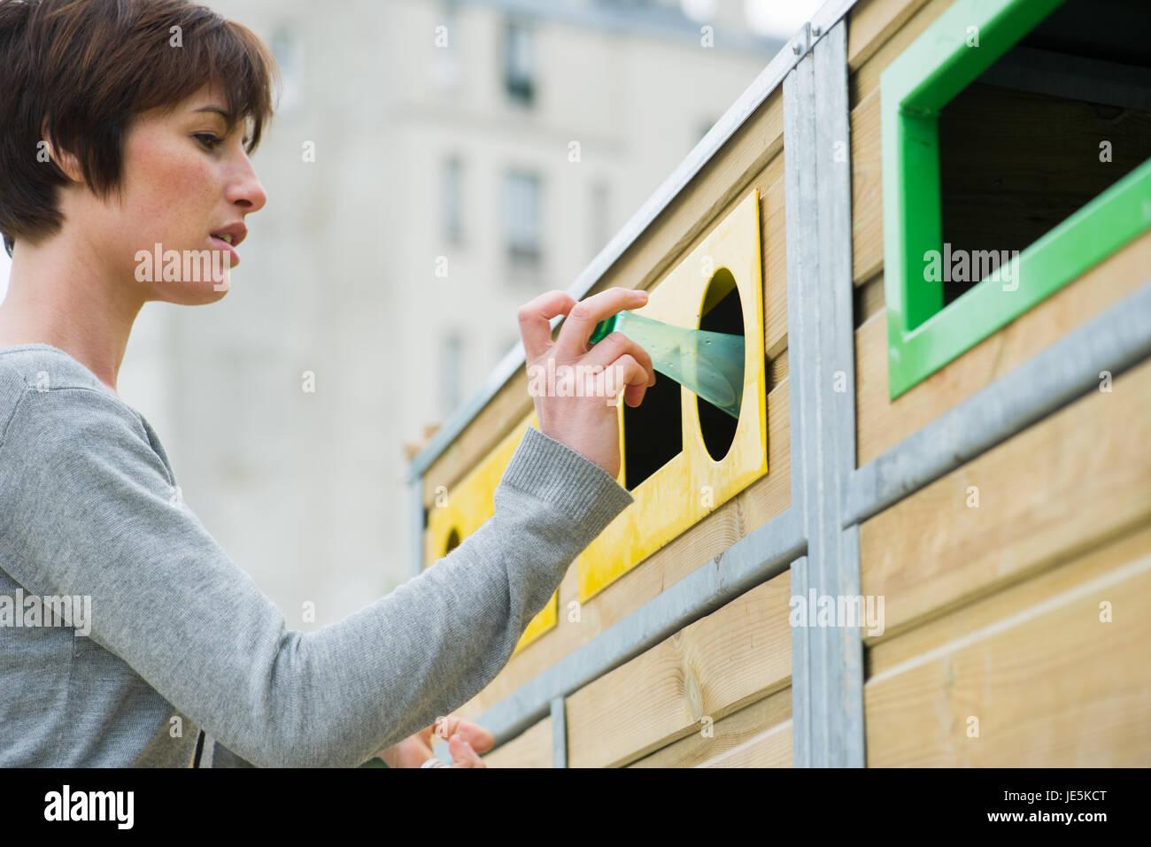 Donna posizionando la bottiglia di plastica nel contenitore di riciclaggio Immagini Stock
