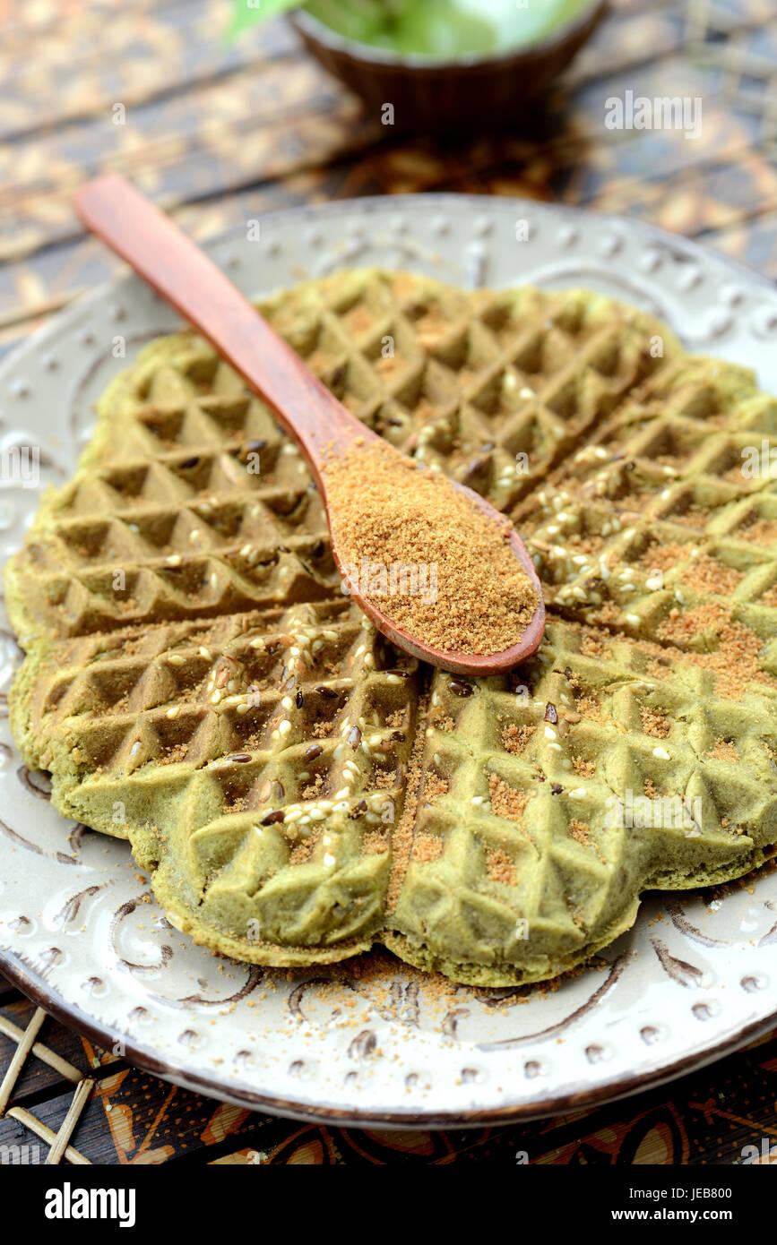 Waffles fatti in casa con aggiunta di matcha, pistacchi semi di lino. Decorata con zucchero di cocco. Immagini Stock