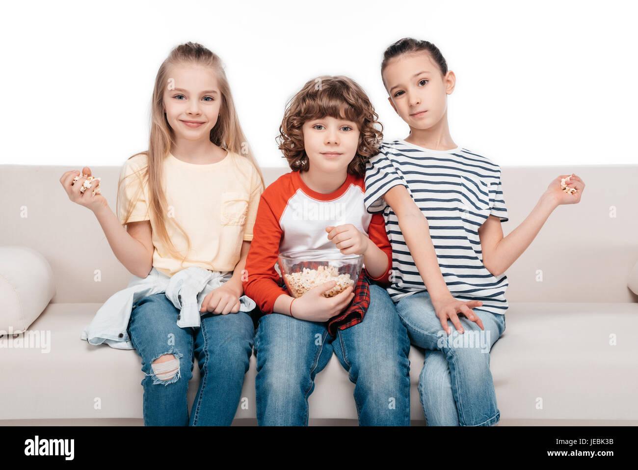 Allegro amici seduti sul divano con pop-corn Immagini Stock