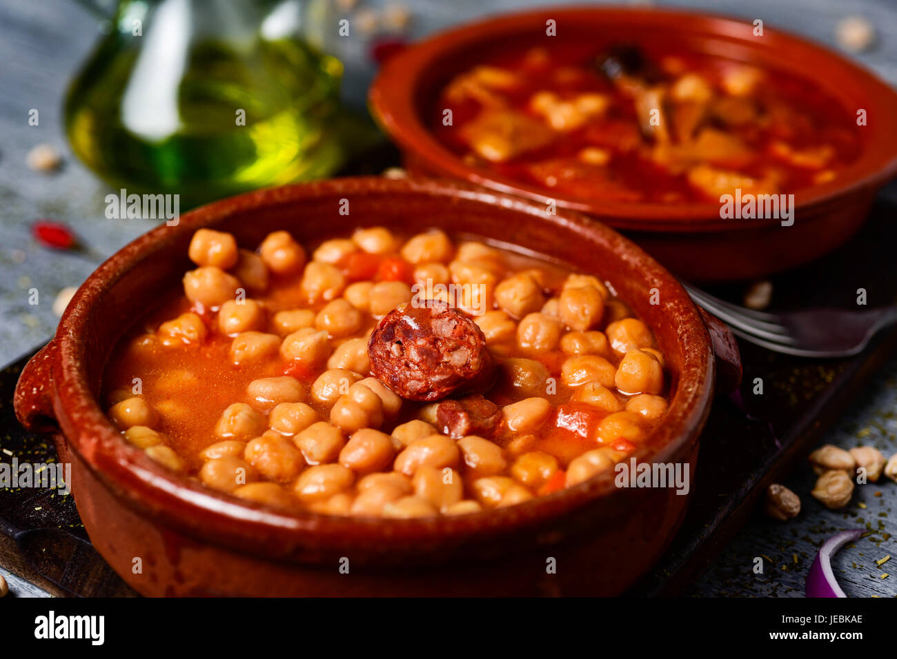 Primo piano di un vaso di terracotta con potaje de garbanzos, uno stufato di ceci con chorizo e prosciutto Serrano Immagini Stock
