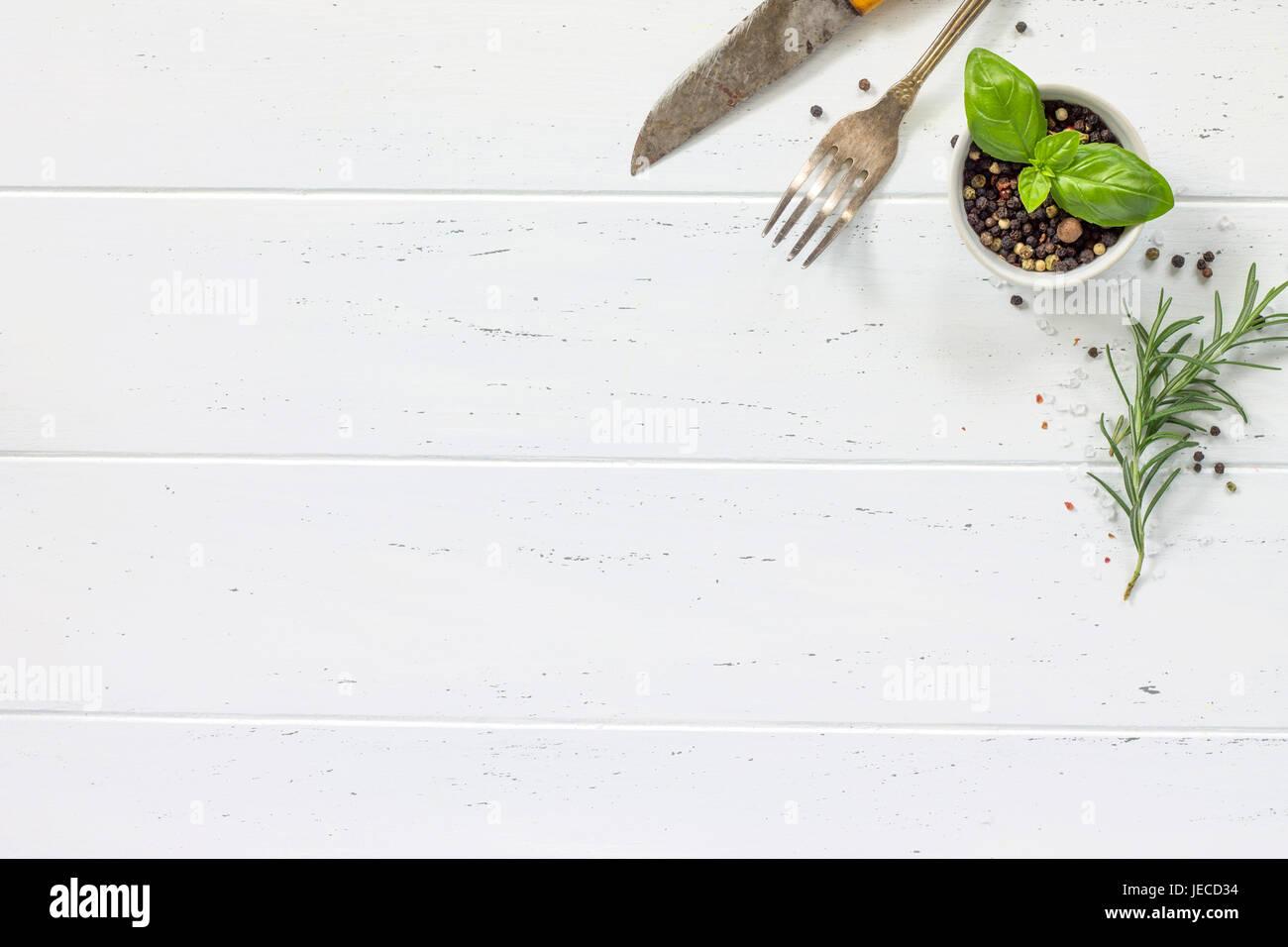 Legno bianco tavolo da cucina. Sullo sfondo la cucina con le erbe aromatiche e le spezie, copia spazio, vista dall'alto. Immagini Stock