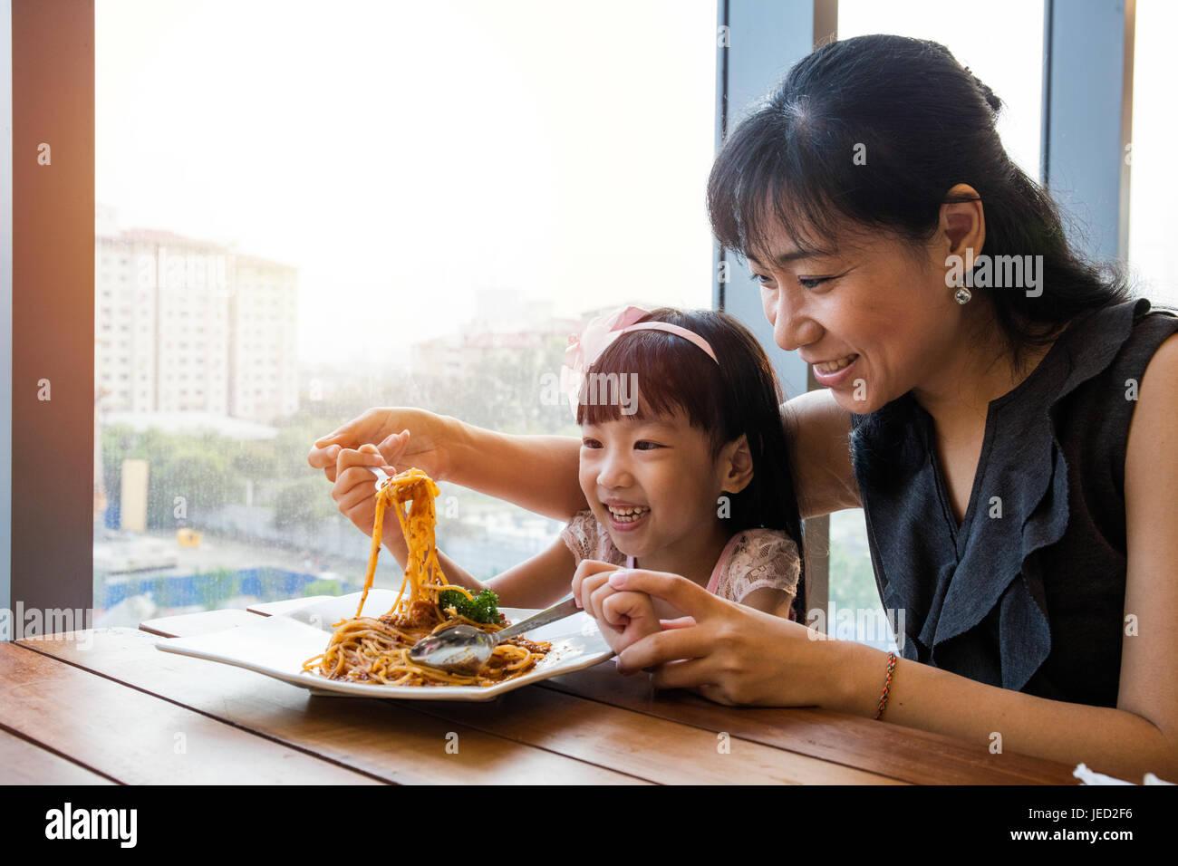 Asian madre cinese e la figlia di mangiare spaghetti alla bolognese nel ristorante. Immagini Stock