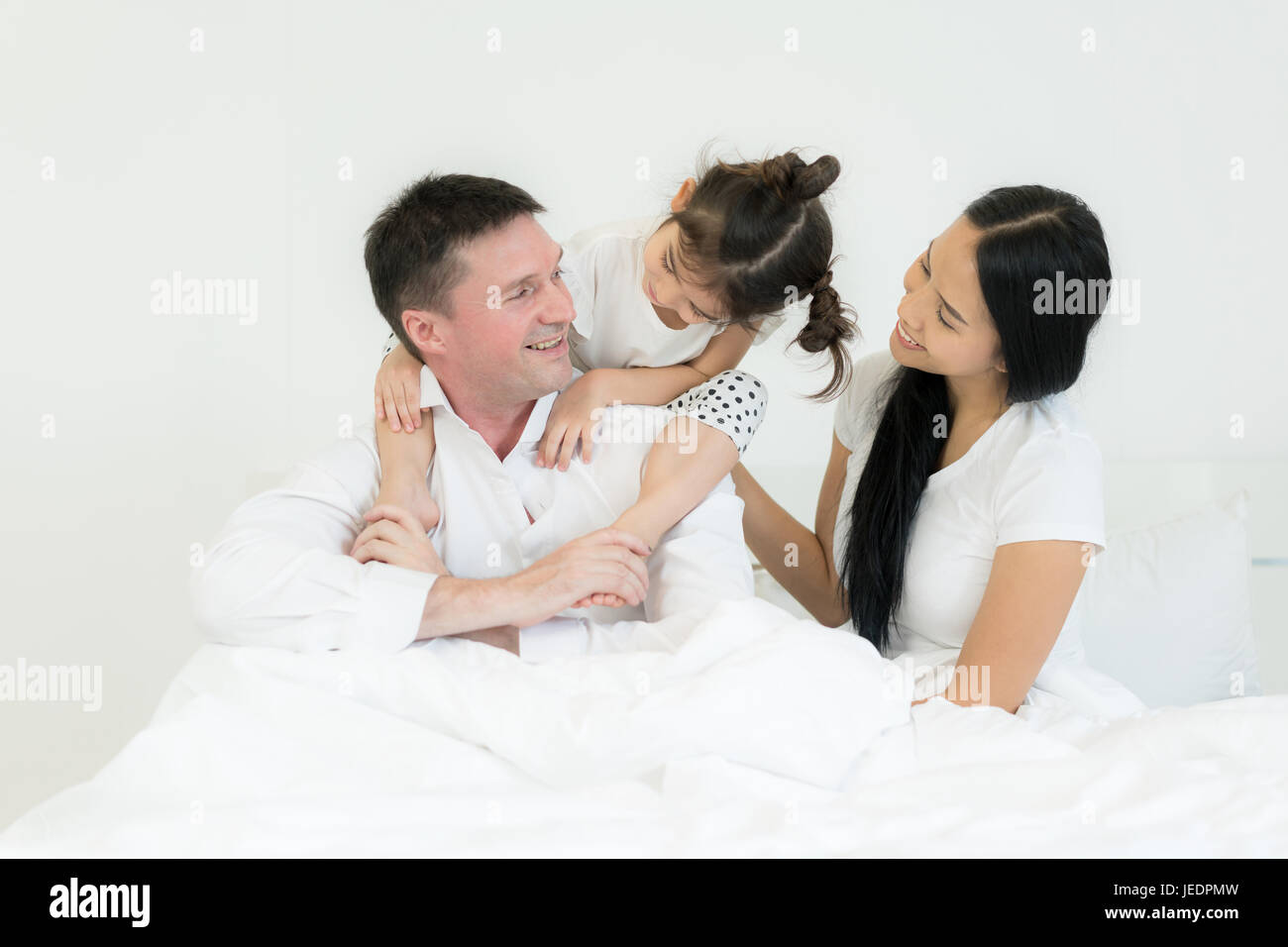 Famiglia con madre Bella e bello padre con incantevole piccola figlia sta parlando e sorridere mentre di trascorrere Immagini Stock