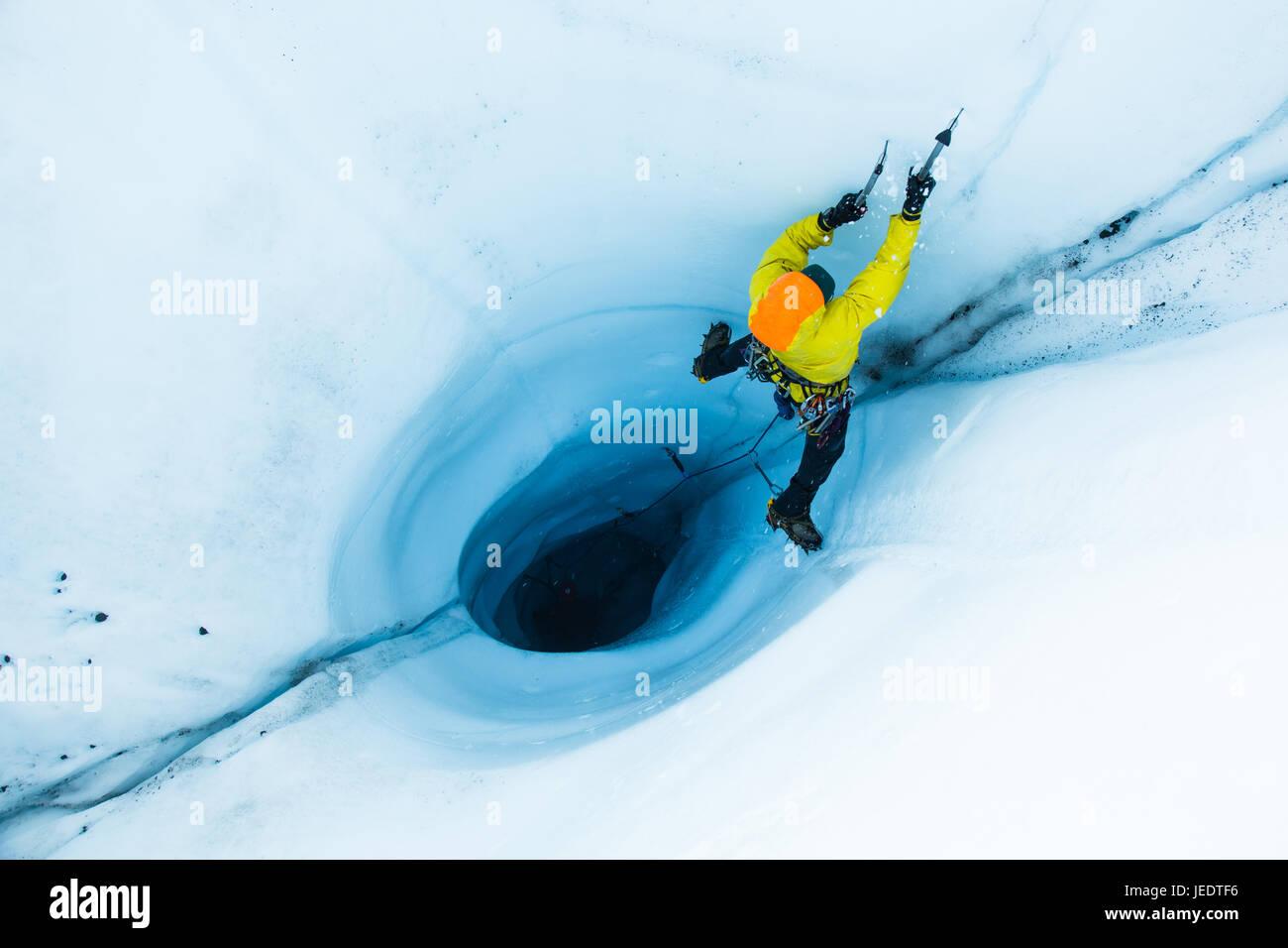 Un uomo portare arrampicata su ghiaccio al di fuori di un grande moulin o buco nel ghiaccio del ghiacciaio Matanuska Foto Stock