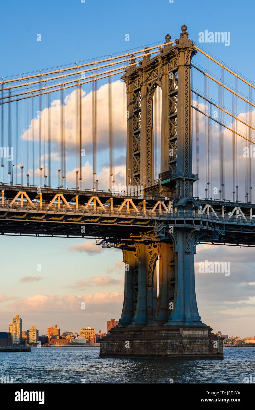 Dettaglio del Manhattan Bridge east tower oltre l'East River al tramonto. La città di New York Immagini Stock
