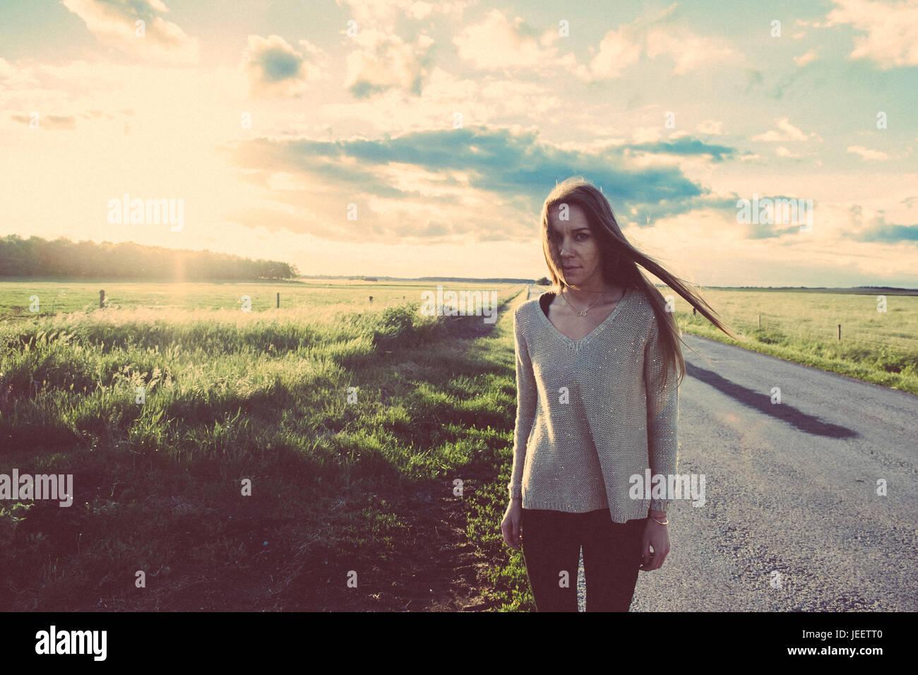 Pellicola fotografica di donna sulla strada in estate tramonto Immagini Stock