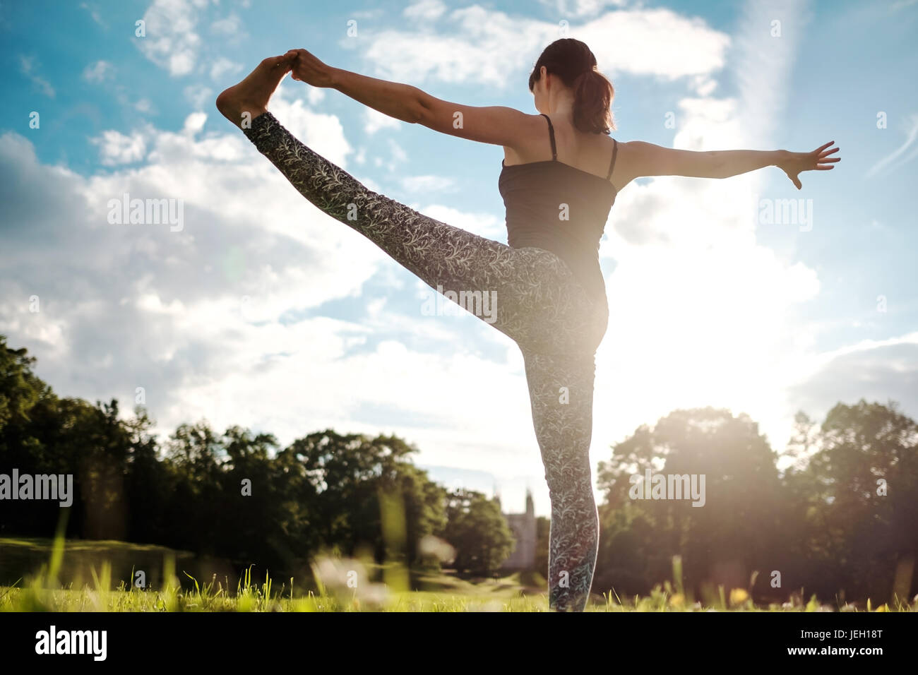 La donna caucasica yoga in permanente equilibrio Utthita Hasta Padangusthasana pongono. Vista posteriore Immagini Stock