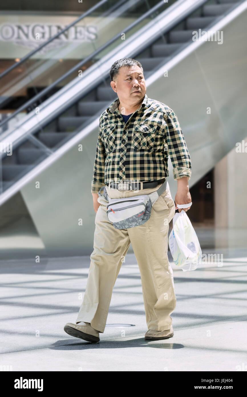 Pechino-Maggio 18, 2016. Il sovrappeso uomo cammina nel centro commerciale per lo shopping. Il girovita medio cinese Immagini Stock