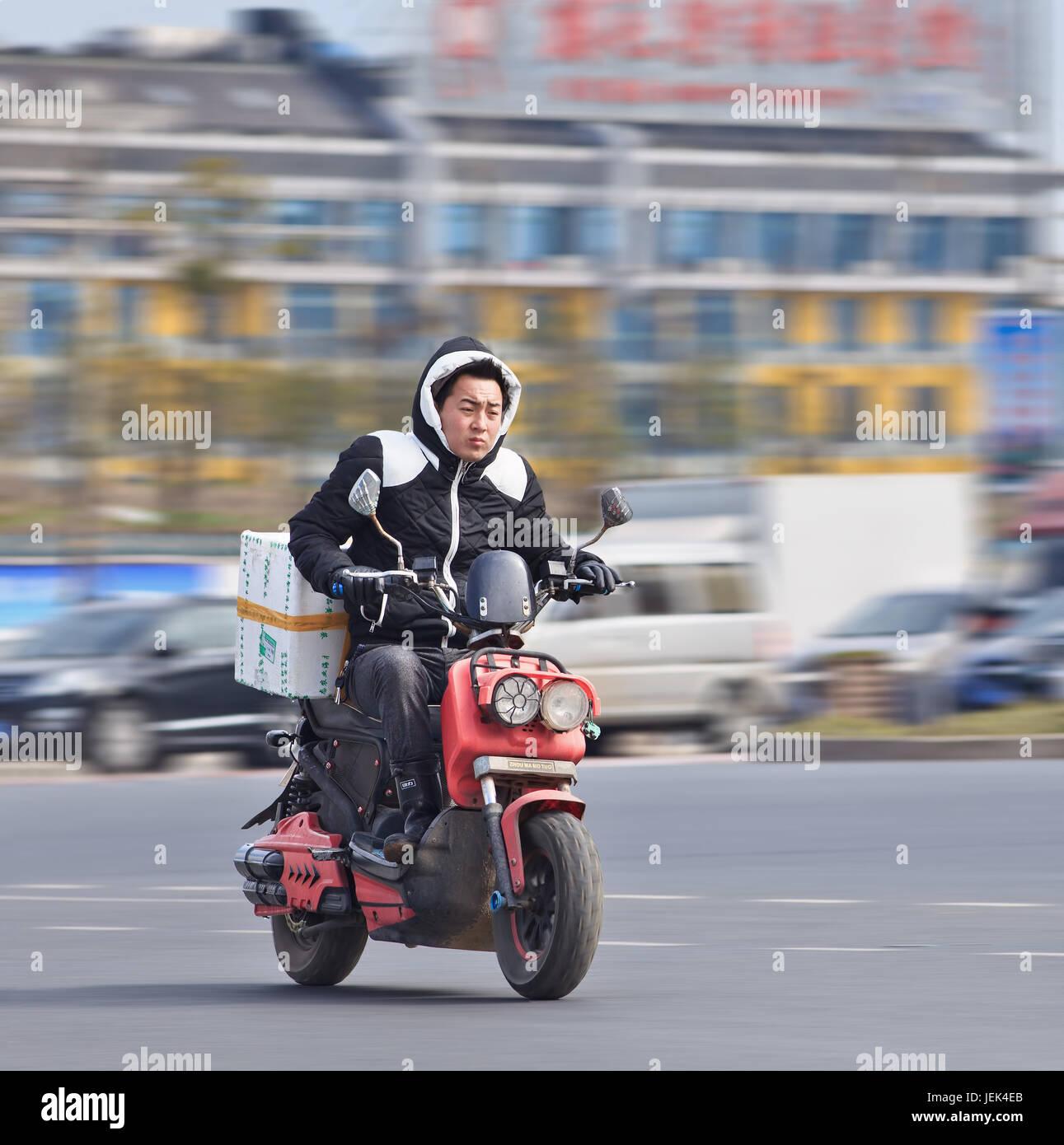 Di YIWU-cina-gen. 26, 2016. Un uomo su un gas scooter. Il Governo vuole vietare uscire i gas scooter e motociclette Immagini Stock