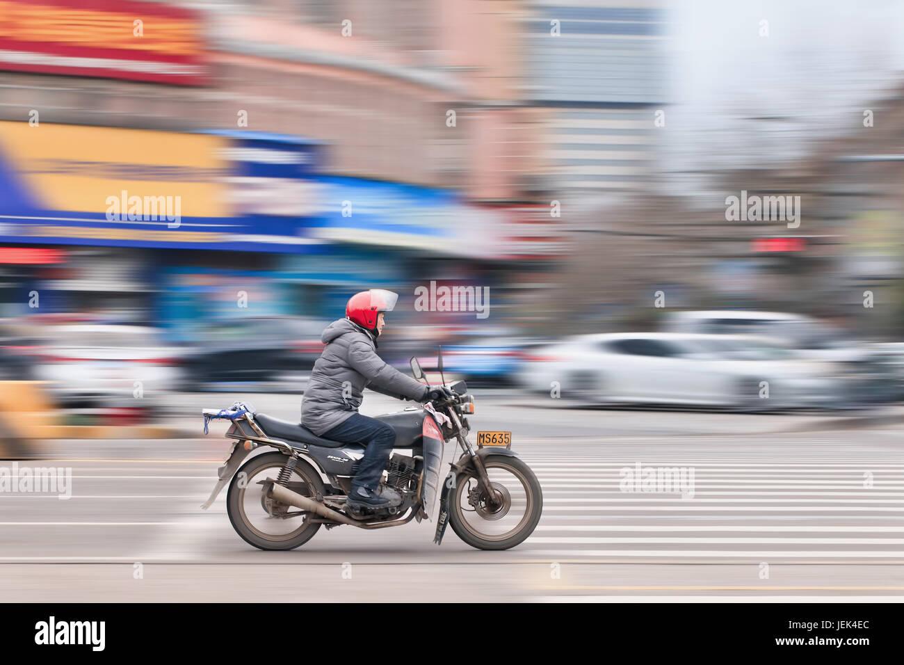 Di YIWU-cina-gen. 26, 2016. Un uomo su una moto. Il Governo vuole vietare uscire i gas scooter e motociclette che Immagini Stock