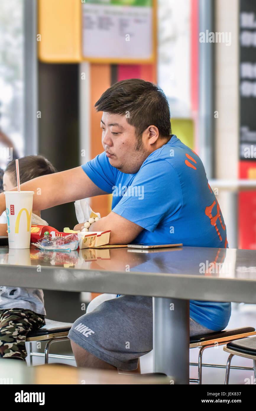 Pechino-Giugno 5, 2016. Uomo al MacDonald's. Cultura Fast food in Cina ha causato il sovrappeso comune. Il girovita Immagini Stock