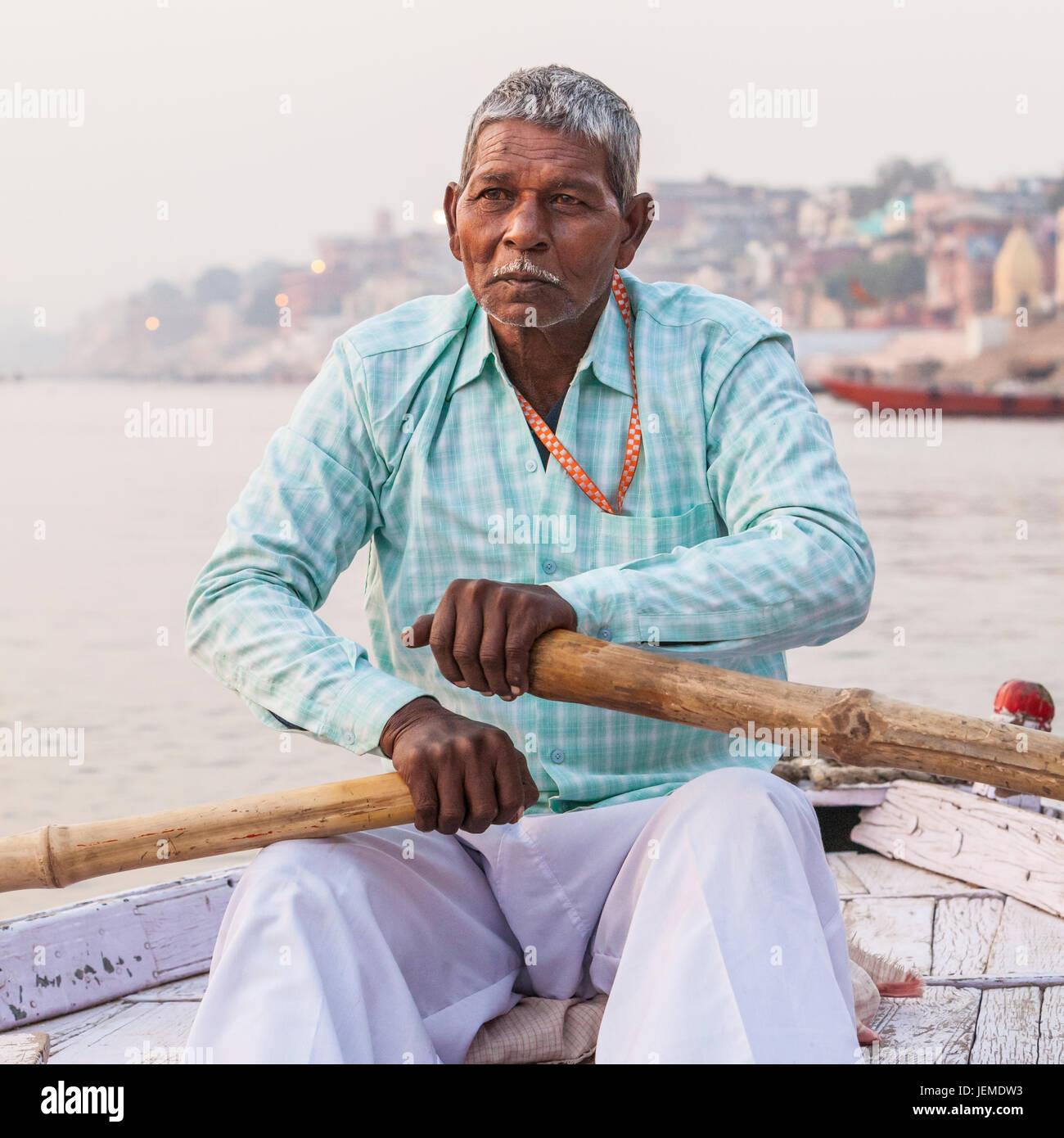 Un uomo indiano remare una barca per escursioni sul fiume Gange, Varanasi (India). Immagini Stock