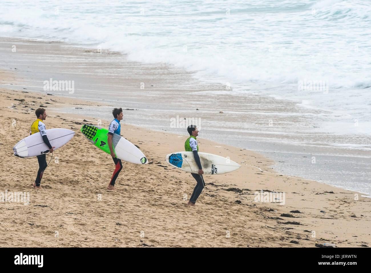 Surf uk. tre surfers permanente sulla fistral beach in attesa di competere in un surf concorrenza., newquay cornwall. Immagini Stock