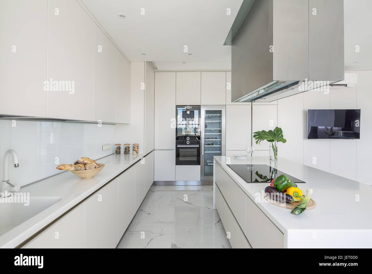 Elegante cucina bianco con pavimento in piastrelle chiare ci sono