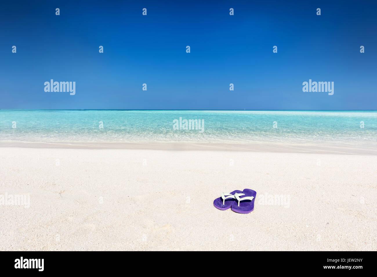 Flip-flop sulla sabbia sulla spiaggia tropicale, chiaro oceano turchese delle Maldive. Le vacanze, per i viaggi Immagini Stock