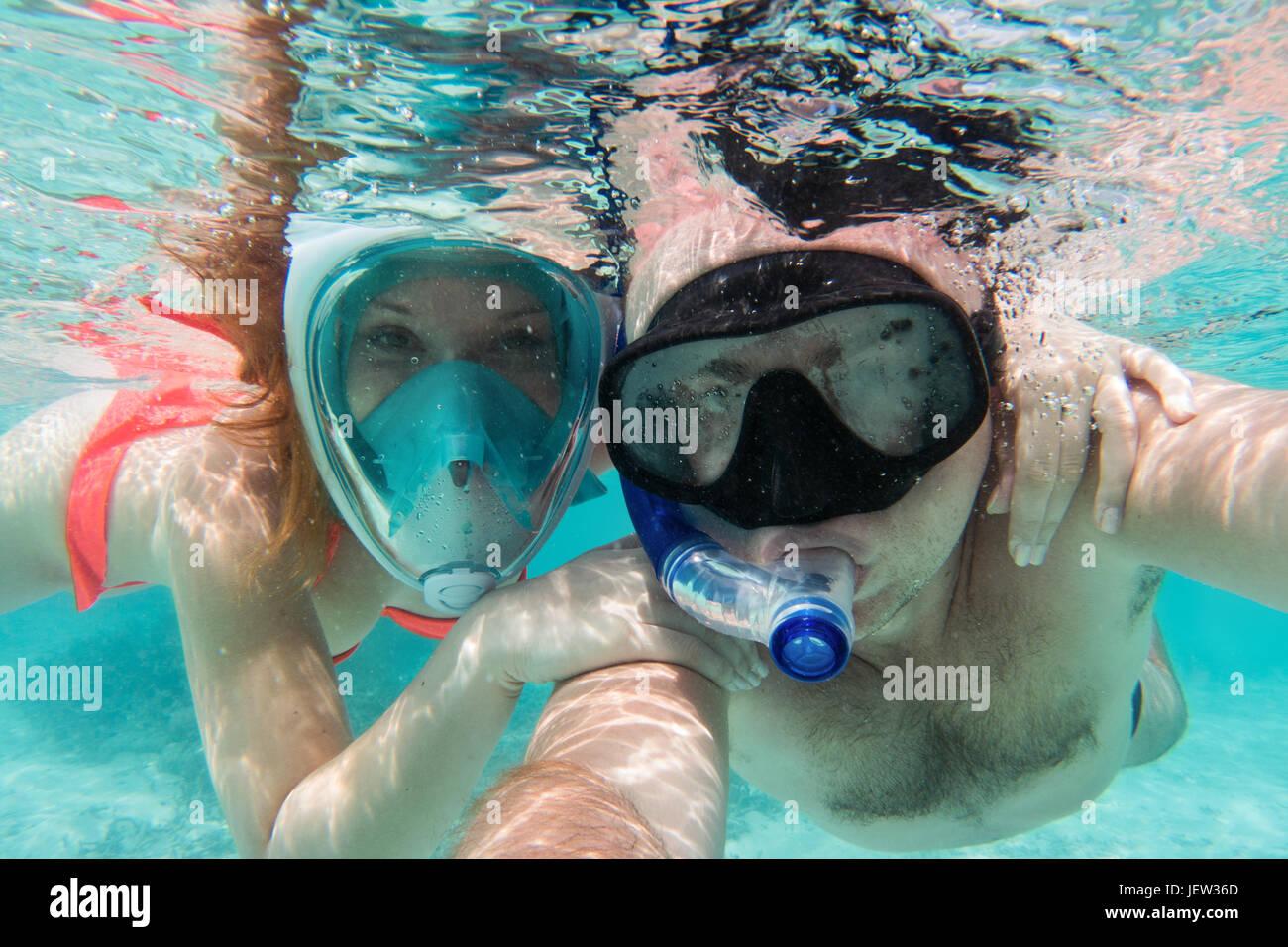 Una coppia in amore selfie tenendo sott'acqua in Oceano Indiano, Maldive. Turchesi acque cristalline. Immagini Stock