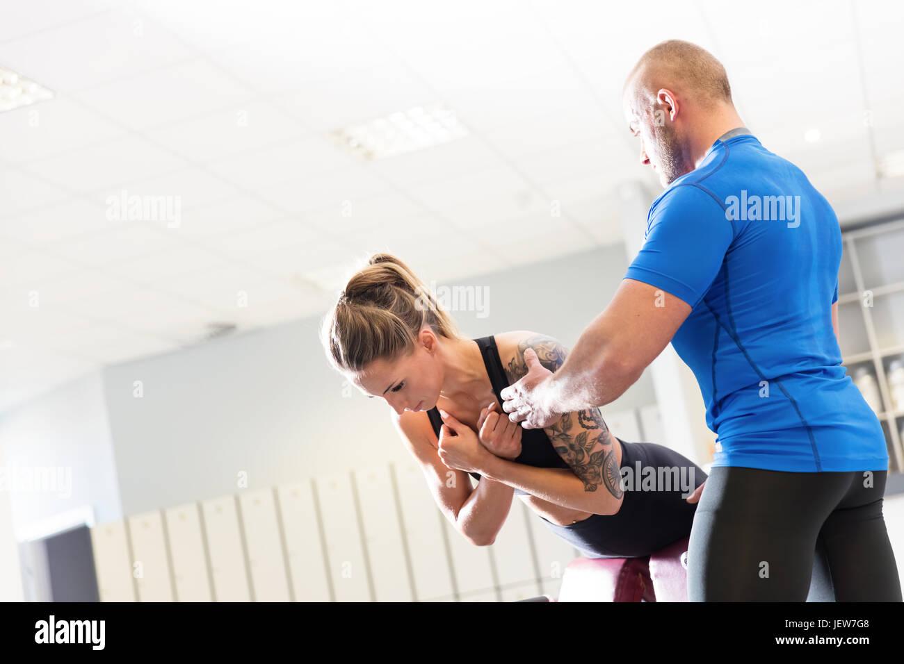 Personal trainer lavora con un client presso la palestra. Assistenza di allenamento e di motivazione. Sport concept. Foto Stock