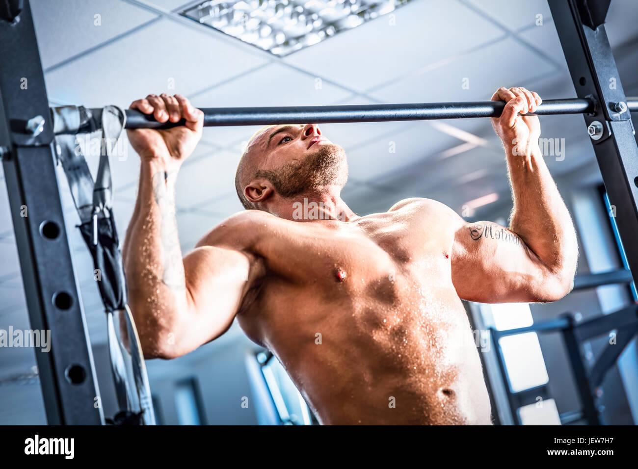 Muscoloso uomo forte della formazione in una palestra a. Crossfit chinup formazione. Bodybuilding e fatburning. Immagini Stock