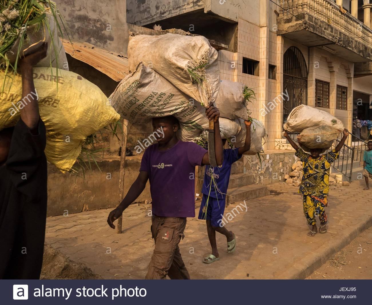 Persone che trasportano grandi carichi sulle loro teste in una strada di Porto Novo. Immagini Stock