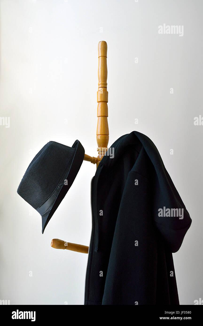 Appendiabiti con un cappello nero e un nero felpa con cappuccio contro il muro Immagini Stock