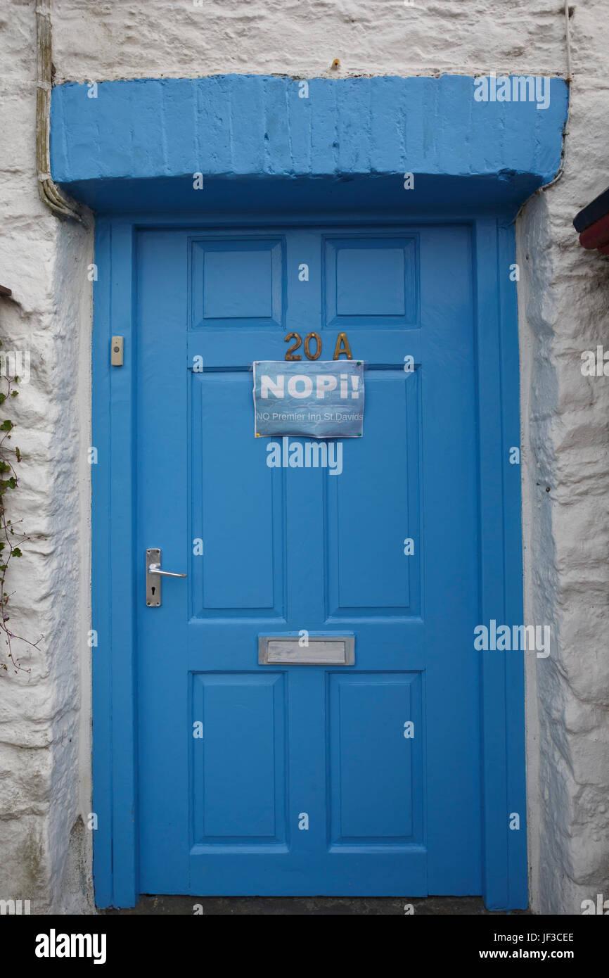 """'Nessun Premier Inn St. David's"""" (NOPi) segno di protesta sulla porta blu, St. David's Pembrokeshire, Immagini Stock"""