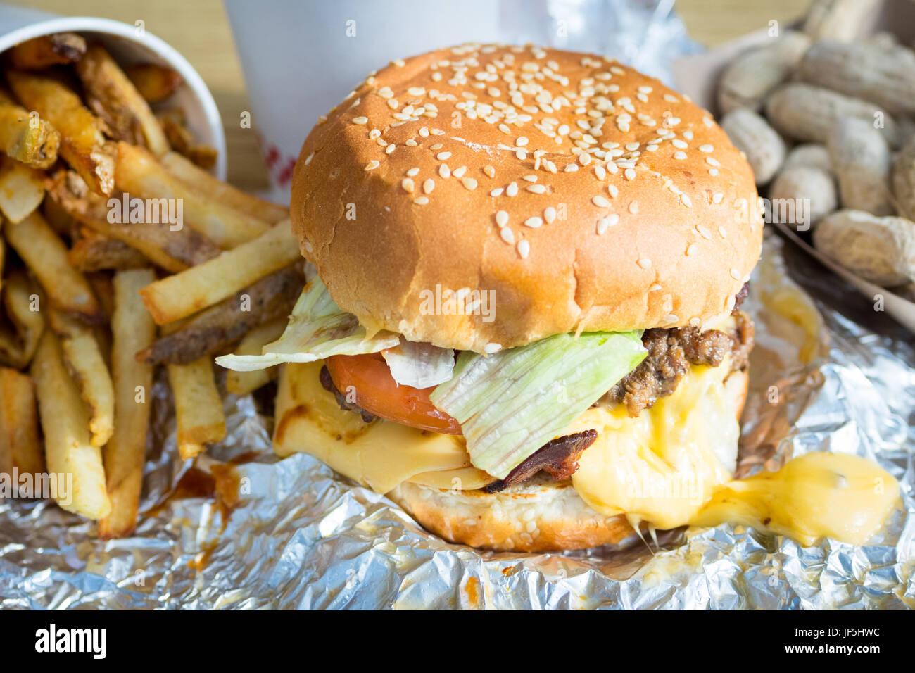 Un bacon cheeseburger, le patatine fritte e arachidi da cinque ragazzi hamburger e patatine fritte, un American Immagini Stock